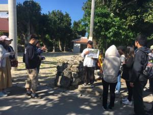 集落ガイドより、「オーセ」という昔、村の役所であった場所にて奉納行事である棒術の説明を聞く学生の皆さん